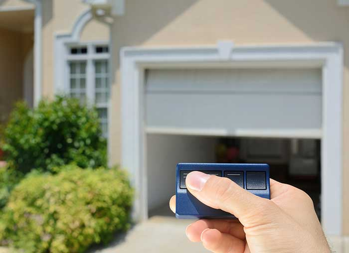 remote opening white garage door to house